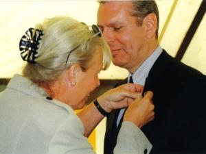 2000 - Erik wordt ere-lid. Ada spelt de versierselen op